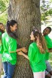 Écologistes se tenant autour du tronc d'arbre Image libre de droits