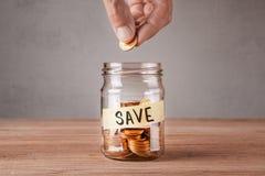 économiser Pot en verre avec des pièces de monnaie et des économies d'inscription L'homme tient la pièce de monnaie dans sa main photographie stock