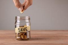 économiser Pot en verre avec des pièces de monnaie et des économies d'inscription L'homme tient la pièce de monnaie dans sa main images libres de droits