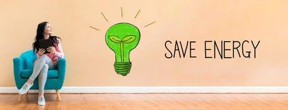Économisez l'énergie avec la femme à l'aide d'un comprimé photo stock