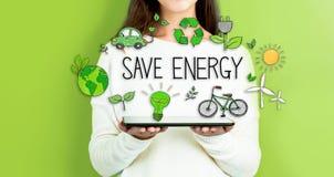 Économisez l'énergie avec la femme tenant un comprimé photos libres de droits
