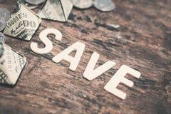 Économisez sur la table en bois avec l'argent photo stock