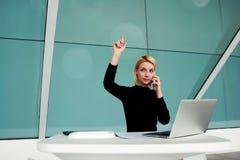 Économiste sûr féminin téléphonant par l'intermédiaire du téléphone de cellules tout en se reposant à la table avec le filet-livr photo libre de droits