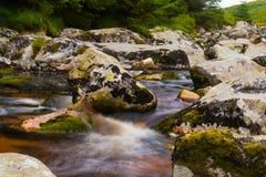 Écoulement d'eau par des roches photo stock