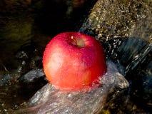 Écoulement de l'eau avec Apple rouge Images libres de droits