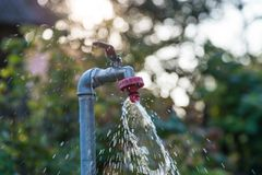 Écoulement de l'eau sur le robinet de jardin sur le fond naturel vert image libre de droits