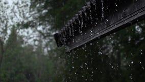 Écoulement de pluie des gouttières d'une maison à la terre banque de vidéos
