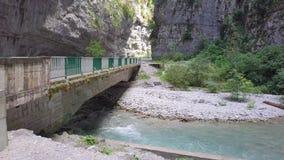 Écoulement rapide de rivière de montagne sous le vieux pont automatique en l'Abkhazie photographie stock libre de droits