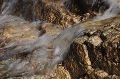 Écoulements d'eau clairs au-dessus des roches roses de granit Image stock