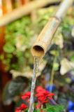 Écoulements d'eau par de petits tuyaux en bambou Photos libres de droits