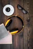 Écoutent le concept d'audiobook Écouteurs près des livres, du café et des verres sur la vue supérieure de fond en bois foncé Images stock