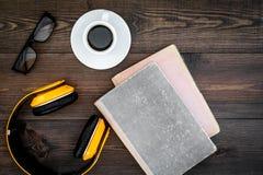 Écoutent le concept d'audiobook Écouteurs près des livres, du café et des verres sur la vue supérieure de fond en bois foncé Image stock