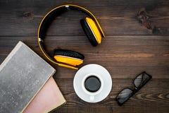 Écoutent le concept d'audiobook Écouteurs près des livres, du café et des verres sur la vue supérieure de fond en bois foncé Photos libres de droits
