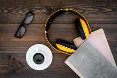 Écoutent le concept d'audiobook Écouteurs près des livres, du café et des verres sur la vue supérieure de fond en bois foncé Photographie stock