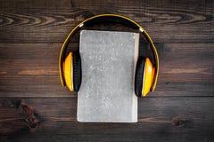Écoutent le concept d'audiobook Écouteurs sur un livre sur l'espace en bois foncé de copie de vue supérieure de fond Images stock