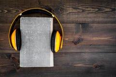 Écoutent le concept d'audiobook Écouteurs sur un livre sur l'espace en bois foncé de copie de vue supérieure de fond Photo libre de droits
