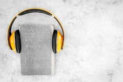 Écoutent le concept d'audiobook Écouteurs sur un livre sur l'espace gris de copie de vue supérieure de fond Image libre de droits