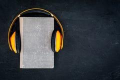 Écoutent le concept d'audiobook Écouteurs sur un livre sur l'espace noir de copie de vue supérieure de fond Photo libre de droits
