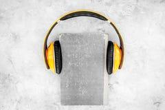 Écoutent le concept d'audiobook Écouteurs sur un livre sur la vue supérieure de fond gris Image stock
