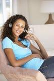Écouter de détente de jeune femme la musique à la maison Photo stock