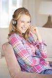 Écouter de détente de jeune femme la musique à la maison Photographie stock