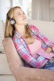 Écouter de détente de jeune femme la musique à la maison images libres de droits