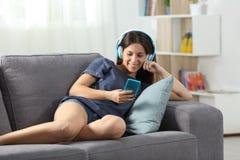 Écouter de l'adolescence heureux la musique avec le téléphone et les écouteurs Photo stock