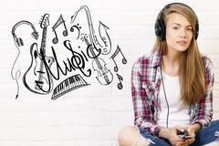 Écouter femelle caucasien la musique photographie stock