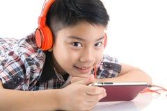 Écouteur asiatique d'articles de garçon et jouer le téléphone portable Photographie stock