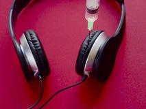 Écouteur avec la seringue - adonnez-vous au concept de musique Images stock