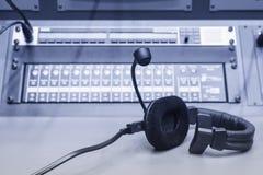 Écouteur avec le pupitre de commande de mélangeur de musique dans le studio Photos stock