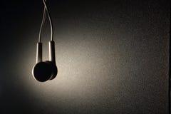 Écouteur blanc avec la lumière brune sur le fond foncé Photo libre de droits