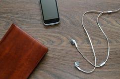 Écouteur, carnet et téléphone blancs sur la table en bois Image stock