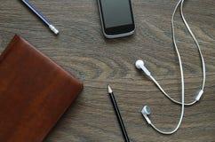Écouteur, carnet, téléphone et crayon blancs sur la table en bois Images libres de droits