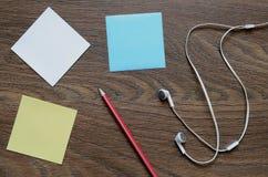 Écouteur, papier et crayon blancs sur la table en bois Photo stock