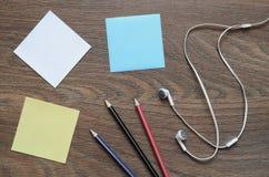 Écouteur, papier et crayon blancs sur la table en bois Image stock
