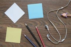 Écouteur, papier et crayon blancs sur la table en bois Photo libre de droits