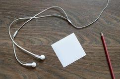 Écouteur, papier et crayon blancs sur la table en bois Image libre de droits