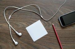 Écouteur, papier, téléphone et crayon blancs sur la table en bois Photos libres de droits