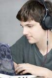Écouteur s'usant les travaux de l'adolescence sur l'ordinateur Image libre de droits