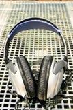 Écouteurs argentés sur le fond argenté de réseau Images libres de droits