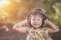 Écouteurs asiatiques d'usage de fille de portrait smilling dans le jardin Co de nature Photos stock