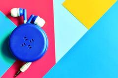 Écouteurs avec la corde extensible sur le fond coloré avec les points culminants au néon image libre de droits