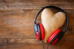 écouteurs avec le coeur de tissu au-dessus du fond en bois Photographie stock