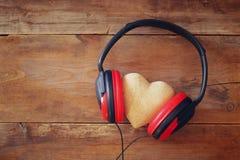 écouteurs avec le coeur de tissu au-dessus du fond en bois Photos libres de droits