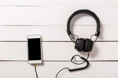 Écouteurs avec le smartphone sur le fond en bois photo stock