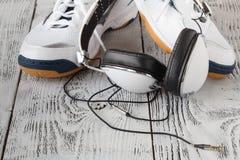 Écouteurs avec les espadrilles et le comprimé sur le fond en bois Images stock