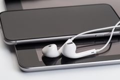 Écouteurs blancs au comprimé et au téléphone photo stock