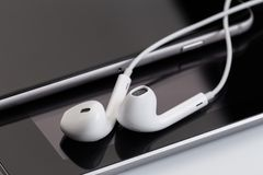 Écouteurs blancs au comprimé et au téléphone photographie stock