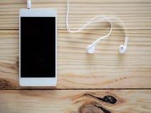 Écouteurs blancs avec des smartphones sur la table et l'espace libre en bois pour le texte et le logo ou les symboles Photographie stock libre de droits